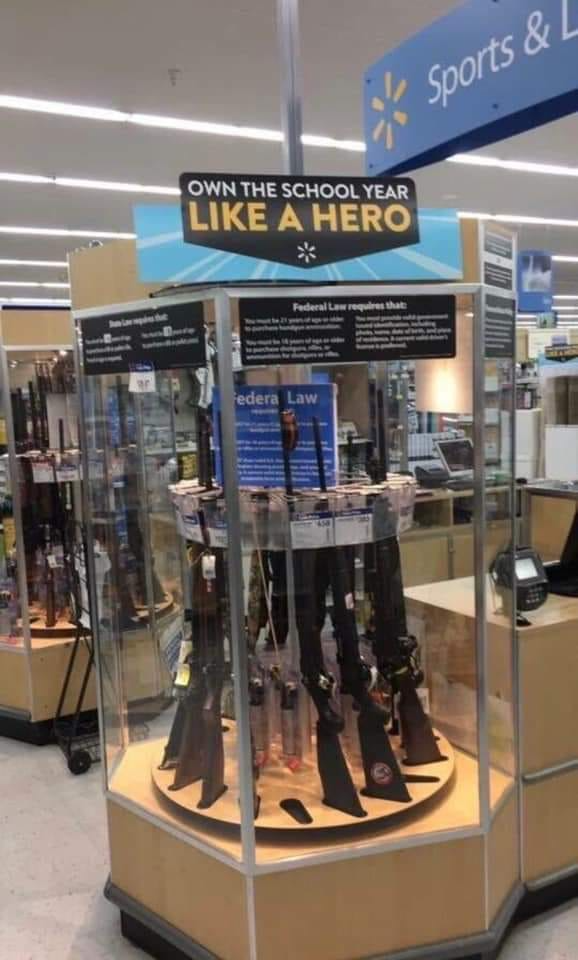 gun display in a walmart, signage over the display reads: Own the School Year Like a Hero